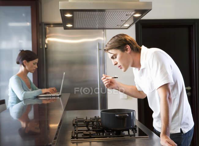 Uomo che cucina in cucina mentre una donna usando il portatile — Foto stock