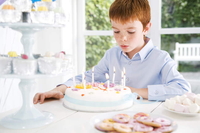 Boy sitting at birthday tea table — Stock Photo
