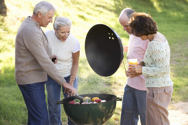 A group of senior friends having a barbeque — Photo de stock