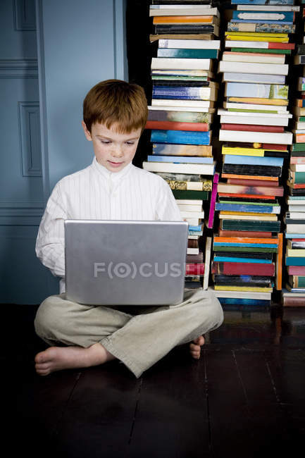 Boy sitting on floor working on laptop computer — Stock Photo