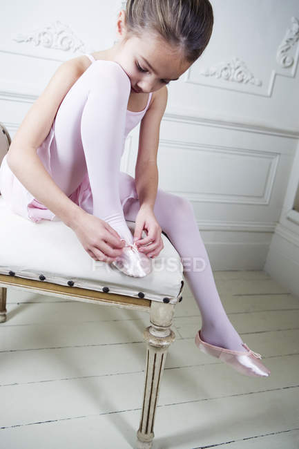Girl sitting on chair and adjusting pointe — Stock Photo