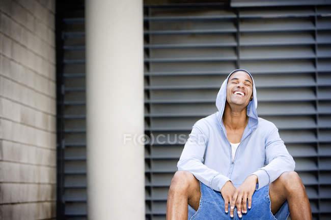 Portrait d'un jeune homme souriant afro-américains dans un haut à capuchon gris, assis sur un ballon de basket — Photo de stock