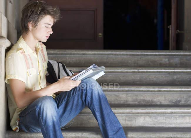 Junger Student sitzt auf der Treppe und Buch — Stockfoto