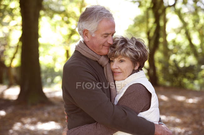 Senior couple hugging in woods — Stock Photo