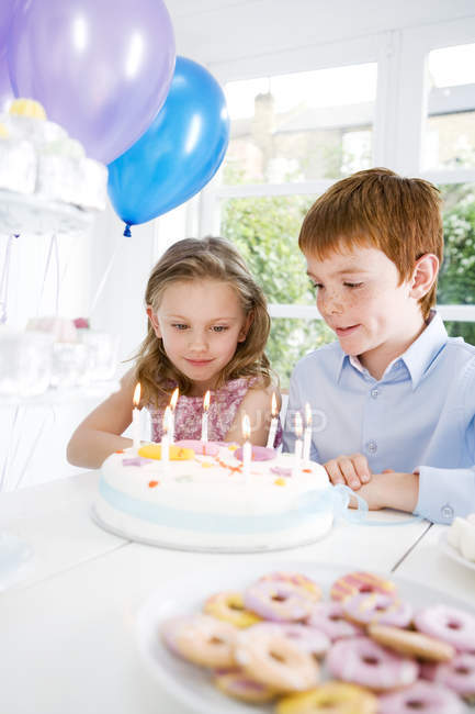 Two children sitting at birthday tea table — Stock Photo