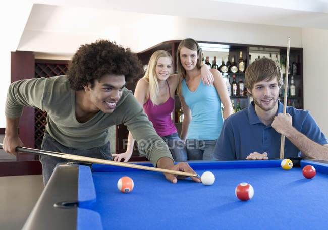 A group of teenage friends playing billiards in a bar — Stock Photo