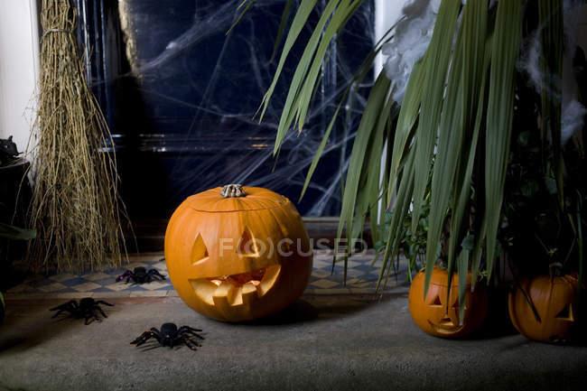 Atmosphérique scène de Halloween - citrouille, manche à balai et les araignées — Photo de stock