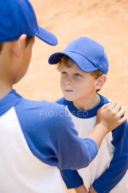 Garçon plus âgé dénigrent au plus jeune garçon à la pratique du baseball — Photo de stock