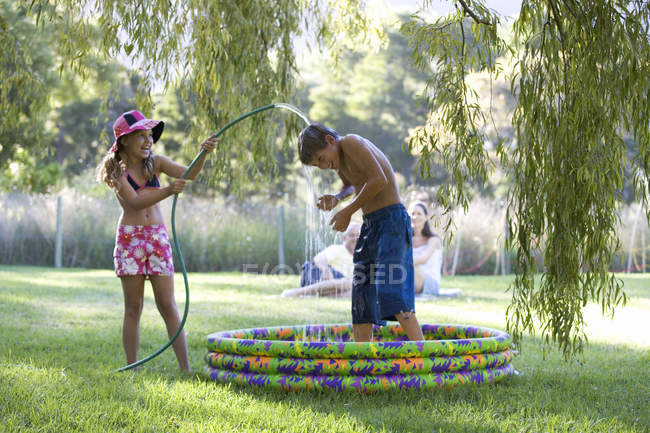 Young girl and boy playing in a paddling pool — Stock Photo