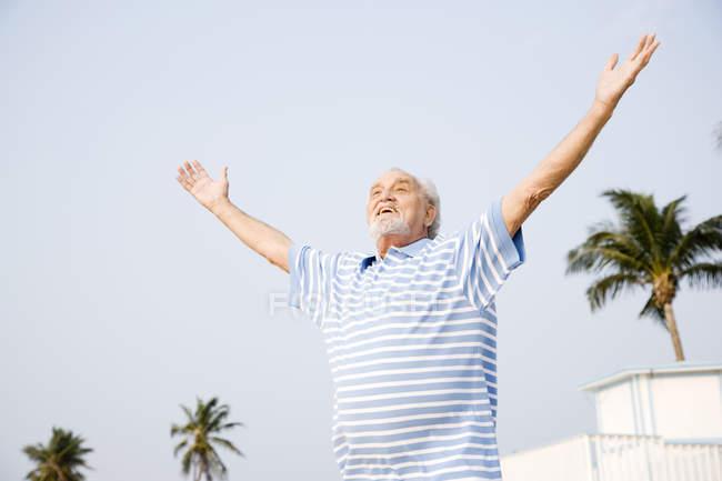 Портрет старший чоловік, що стоїть на пляжі з розкритими обіймами — стокове фото