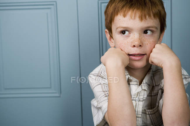 Boy with ginger hair resting face in hands — Stock Photo