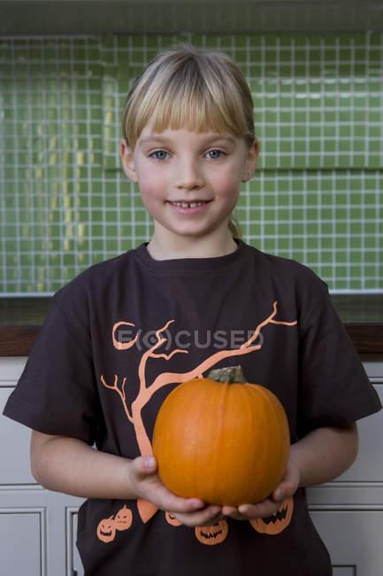 Petite fille tenant un orange citrouille d'Halloween — Photo de stock
