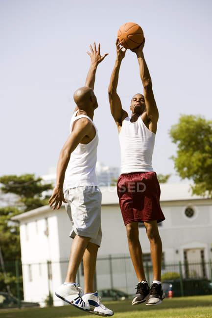 Dois homens Africano-americanos pulando de uma bola de basquete — Fotografia de Stock