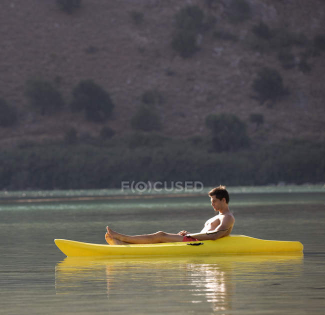 A man relaxing in a canoe at lake — Stock Photo