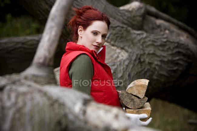Femme tenant du bois de chauffage et en regardant la caméra — Photo de stock