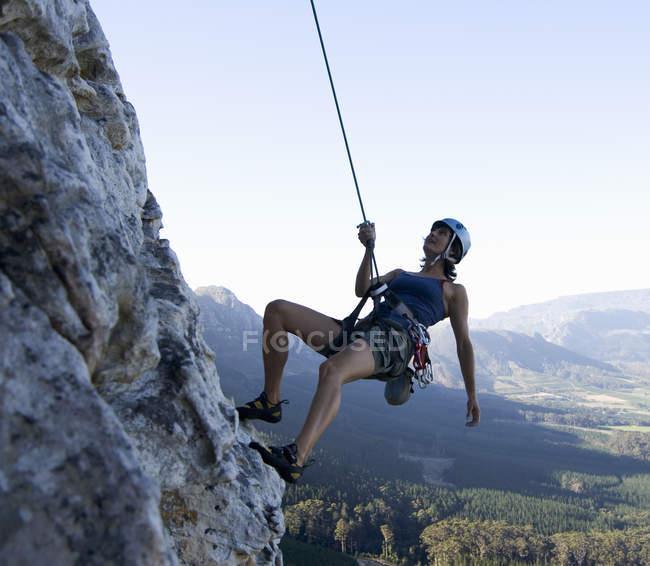 Альпініст жінка альпінізм на скелі — стокове фото