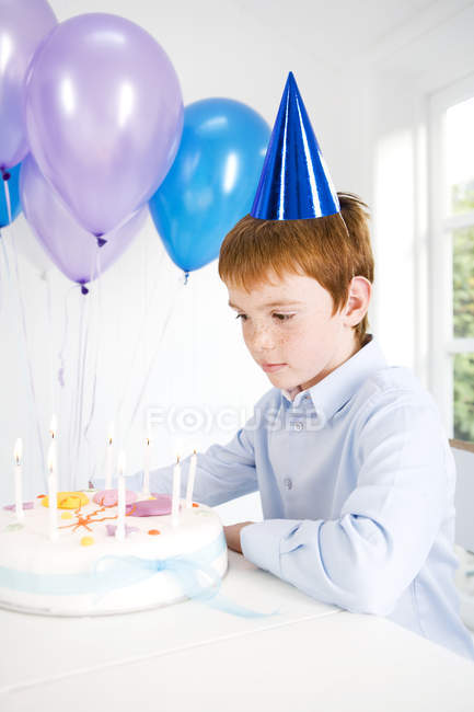 Boy sitting at table with birthday cake and balloons — Stock Photo
