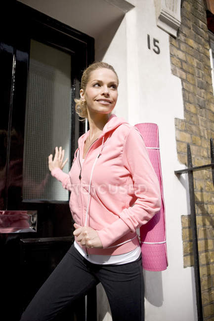 Woman  looking aside and opening door — Stock Photo