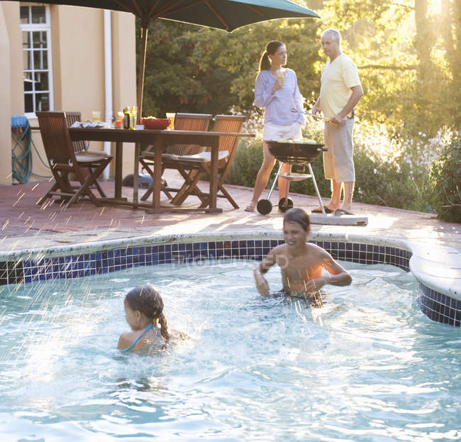 Children swimming in the pool at a family barbeque — Stock Photo
