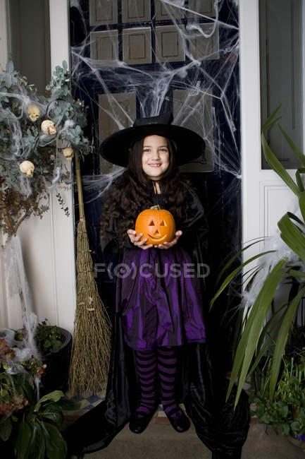 Jeune fille en costume de sorcière lors d'une fête d'Halloween, tenant une citrouille — Photo de stock