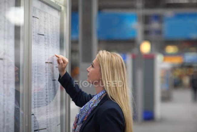Mid adult woman studying train timetable, Munich, Bavaria, Germany, Europe — Stock Photo