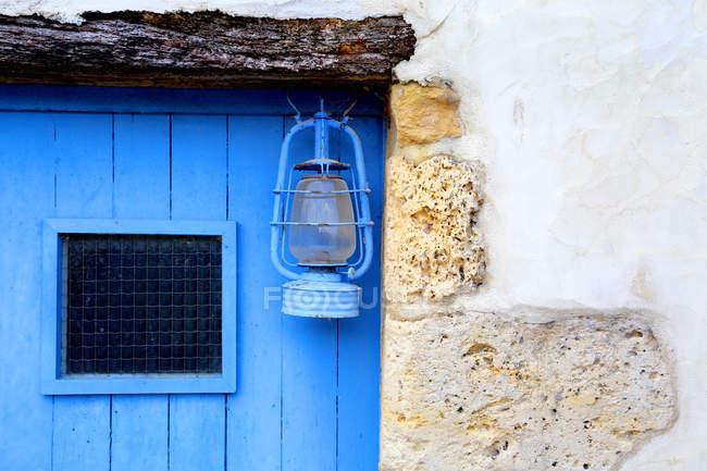 Vintage lantern hanging on blue building — Stock Photo