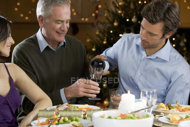 Homem, derramando vinho em vidro para homem sênior — Fotografia de Stock