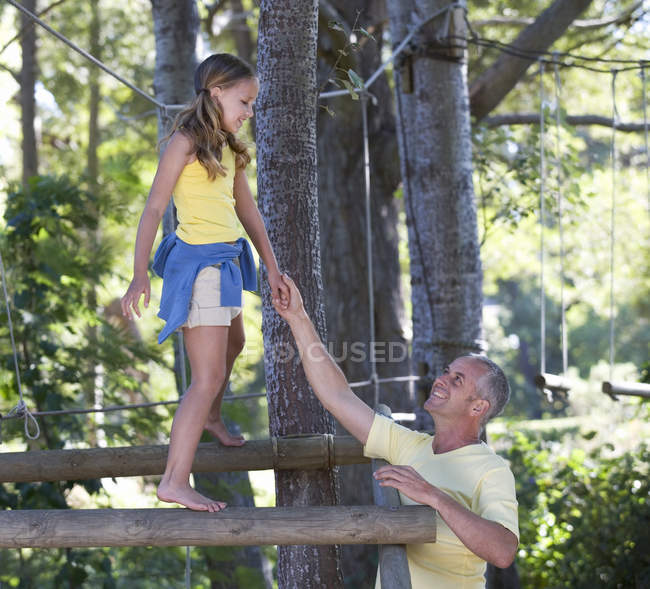 A father helping his daughter balance on a climbing frame — Stock Photo