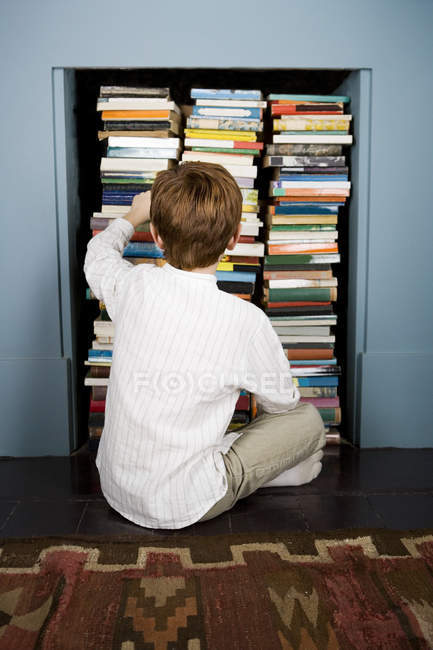 Boy choosing book from bookshelf — Stock Photo