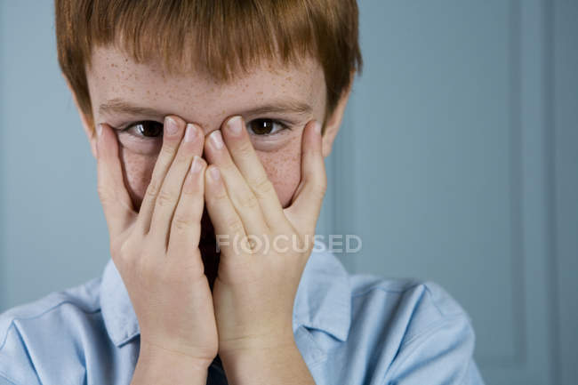 Boy with ginger hair playing peek a boo through fingers — Stock Photo