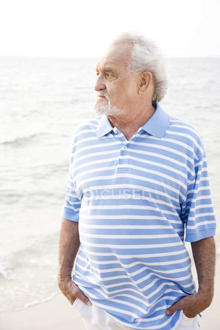 Portrait of a senior man standing on a beach looking thoughtful — Stock Photo