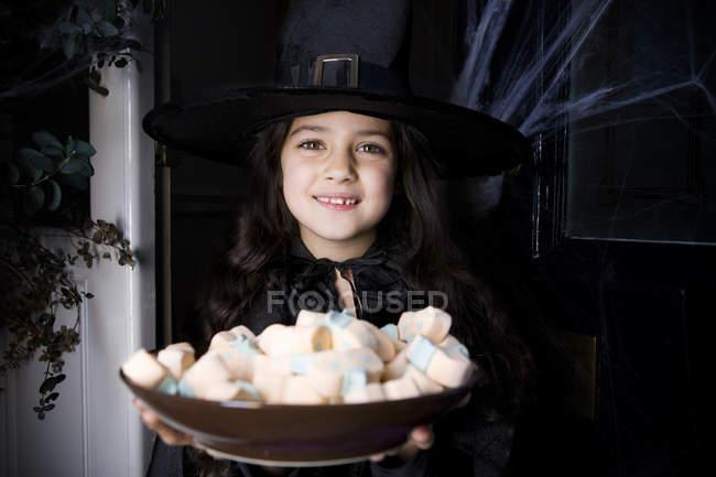 Jeune fille en costume de sorcière lors d'une fête d'Halloween, tenant un plateau de gourmandises — Photo de stock