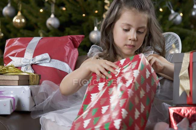 Вид спереди молодая девушка, открытие рождественского подарка — стоковое фото