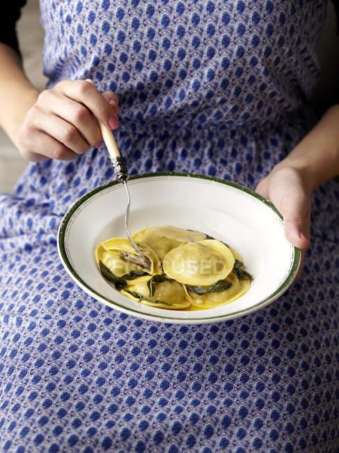 Femmes mains tenant la plaque à raviolis — Photo de stock