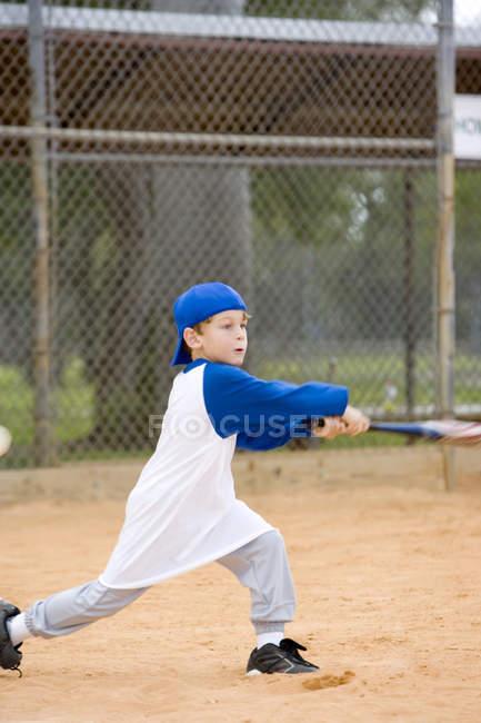 Молодий хлопчик розмахуючи бейсбольною битою — стокове фото