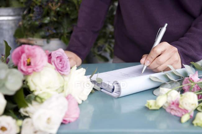 Mains féminines écrire dans cahier — Photo de stock