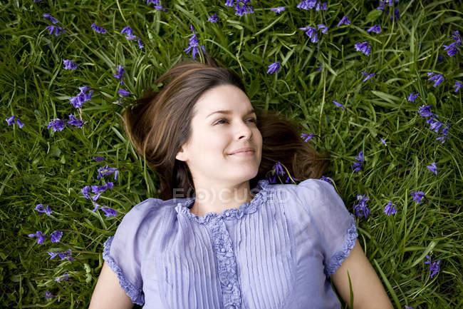 Brunette girl lying among bluebells — Stock Photo