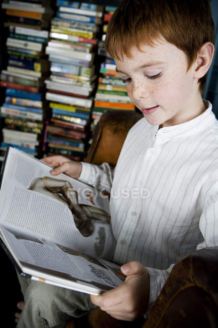 Boy reading book in home library — Stock Photo
