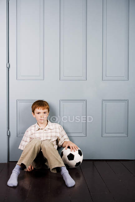 Little boy sitting on floor with football — Stock Photo