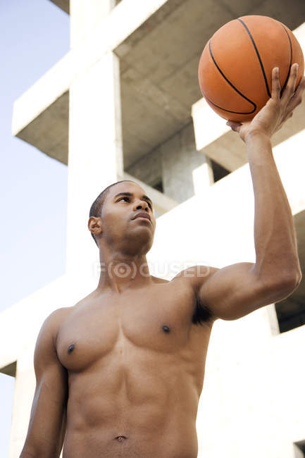 Portrait of a young African American man holding up a basketball. — Stock Photo