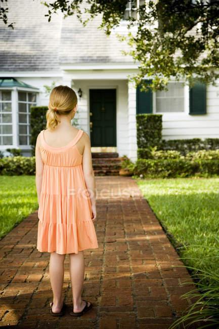Menina de pé no jardim caminho fora de casa — Fotografia de Stock