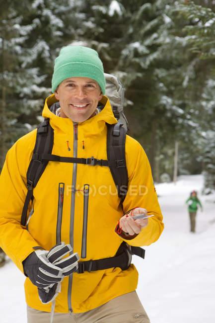 Ritratto dell'uomo sorridente con lo zaino che tiene la bussola in boschi innevati — Foto stock
