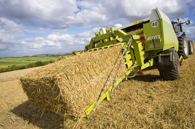 Baler baling straw in rural field — Stock Photo