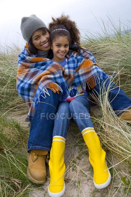 Mãe e filha sentado na grama de praia a sorrir — Fotografia de Stock