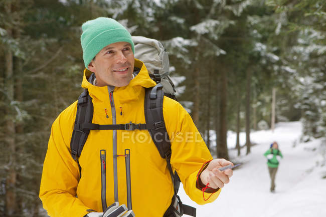 Man with backpack holding compass in snowy woods — Stock Photo