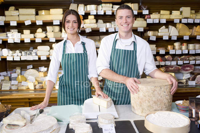 Portrait of smiling salespeople posingat counter with cheese in cheese shop — Stock Photo