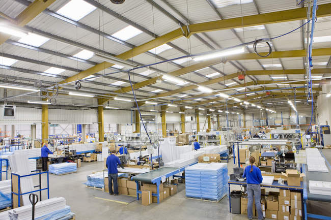 Workers on production line in factory manufactures aluminium light fittings — Stock Photo