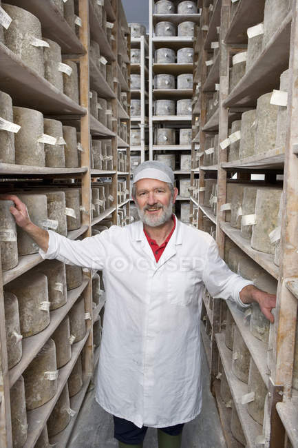 Portrait of senior cheese maker standing among shelves with aged farmhouse cheddar cheese wheels and looking at camera — Stock Photo
