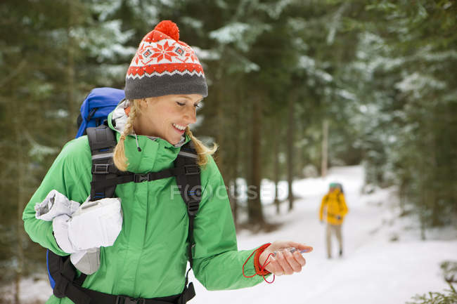 Woman with backpack checking compass in snowy woods — Stock Photo