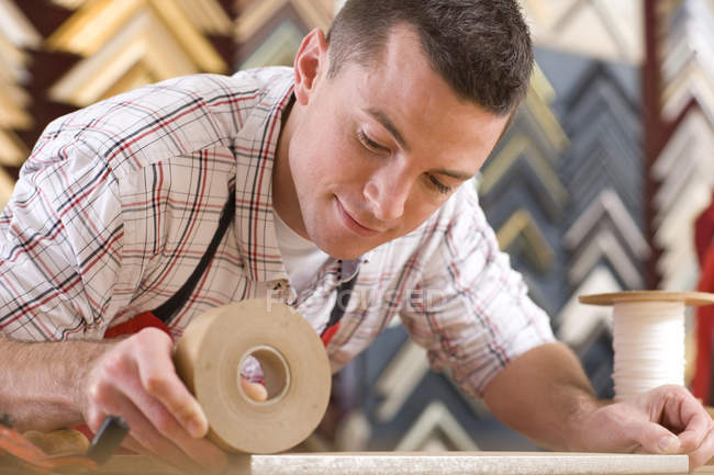 Craftsman working on frame in frame shop — Stock Photo